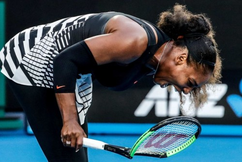 Serena Williams breaks a racquet in frustration during the opening set against sister Venus. AAP Image: Made Nagi